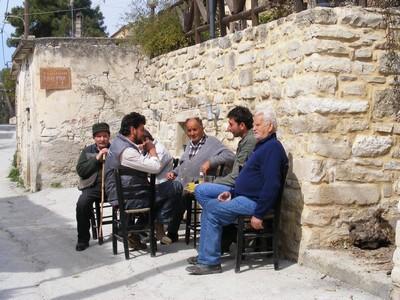 Cretan men chatting on chairs in the street